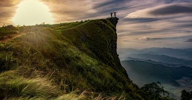 two people stretch on top of a mountain