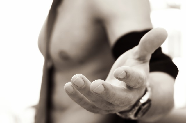 semi-naked man with his hand out, as if waiting to fulfill sexual fantasies