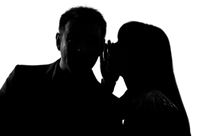 couple hidden in shadows and woman is telling man a secret