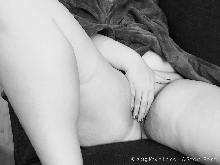 Kayla Lords, naked with her hand on her vulva