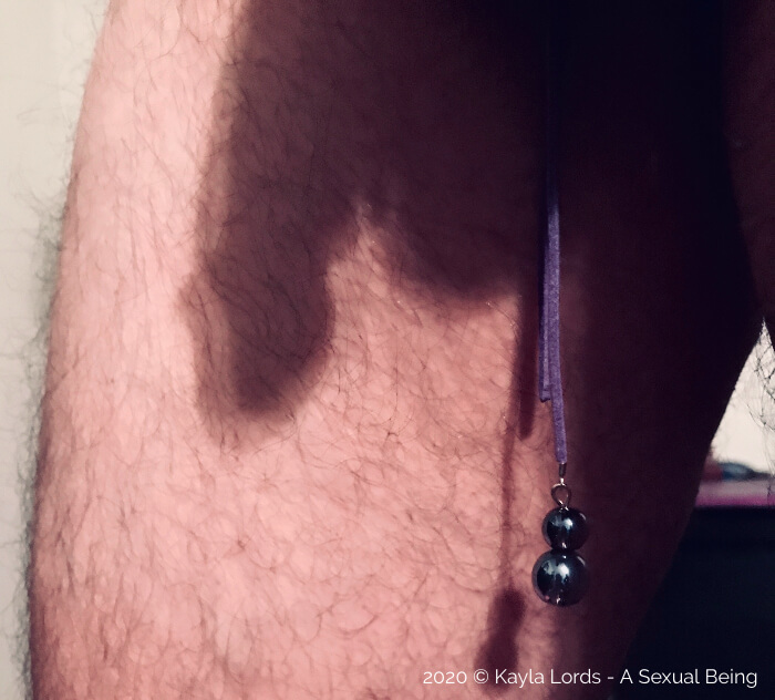 Image of the shadow of John Brownstone's cock and balls against his leg while wearing a purple penis noose