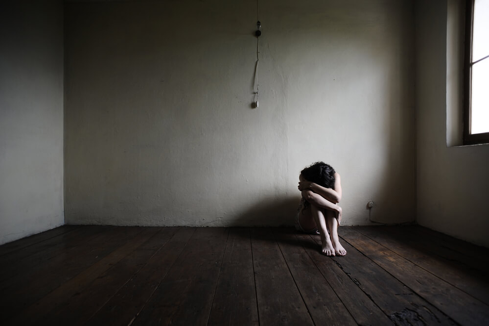 image of woman sitting in corner of a dark, bare room hugging her knees with her head down -- this is how I feel when I'm reminded of past emotional abuse