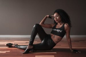 author image for Femme Fatala, a woman of color sitting on the floor wearing an arousr shirt