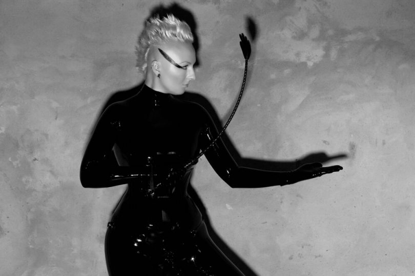 black and white image of blonde femme person wearing latex and holding crop - is she a domme or dominatrix