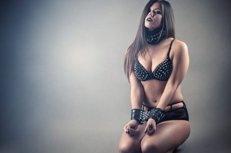 feminine person kneeling while wearing a collar and leather cuffs in a studded leather bikini as part of submission in D/s protocol