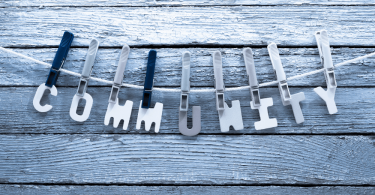 blog banner with the letters spelling out community hung on a line with plastic clothespins in a gray scale image as a concept for finding your kinky community
