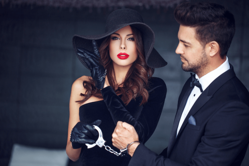image of elegantly dressed woman holding a handcuff that's attached to a man's wrist -- man is in a suit and may be a male escort