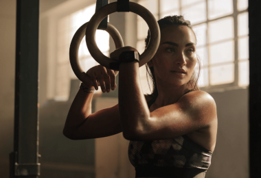 woman in gym with hair pulled back, holding onto rings, arm muscles flexed as concept for central character in erotic fantasy