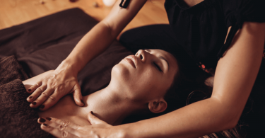 woman lying down on floor with towel covering chest and eyes closed as feminine hands massage her chest with a candle in the background as a concept for tantric massage
